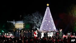 FILE - President Barack Obama, with Michelle Obama, and daughter Sasha, sing with Santa Claus and others during the lighting ceremony for the 2016 National Christmas Tree on the Ellipse near the White House, Dec. 1, 2016.