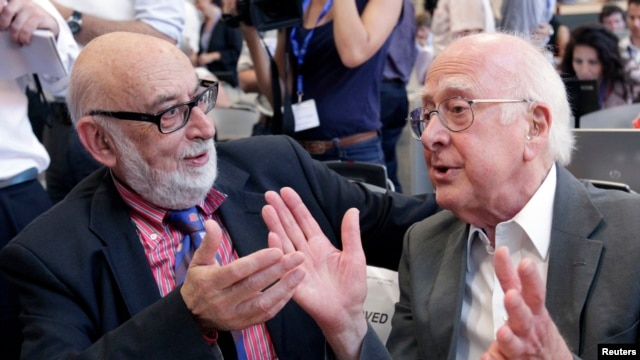 FILE - British physicist Peter Higgs, right, talks with Belgian physicist Francois Englert at CERN news conference, near Geneva, July 4, 2012.