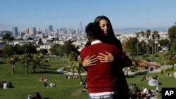 Julie Rajagopal, facing, hugs her 16-year-old foster child from Eritrea after posing for photos at Dolores Park in San Francisco, July 14, 2017. When he landed in March, he was among the last refugee foster children to make it into the U.S. Trump administ