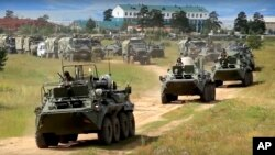 In this frame grab provided by Russian Defense Ministry Press Service on Tuesday, Sept. 11, 2018, Russian armored personnel carriers roll during the military exercises in the Chita region, Eastern Siberia, during the Vostok 2018 exercises in Russia.