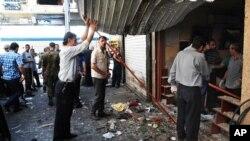 Foto yang dirilis oleh kantor berita Suriah, SANA, ini menunjukkan warga tengah memeriksa toko yang rusak akibat ledakan bom di pusat wilayah al-Marjeh, Damaskus, Suriah (11/6).