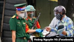 Lực lượng quân đội có vũ trang kiểm tra giấy tờ của người dân tại một chốt kiểm soát ở TPHCM, hiện đang trong thời gian hạn chế nghiêm ngặt vì sự bùng phát dịch COVID-19.