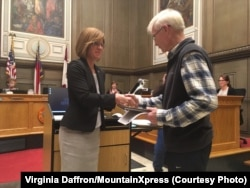 Asheville, North Carolina Mayor Esther Manheimer shakes hands with a local volunteer.