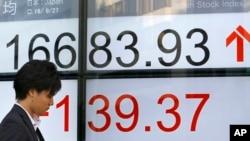 一名男子站在东京一家股票交易所的显示屏前。(2016年9月27日)