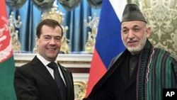 Russian President Dmitry Medvedev, left, shakes hands with Afghan President Hamid Karzai during their meeting in Moscow's Kremlin, Russia, 21 Jan 2011