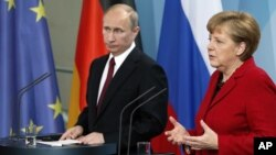 German Chancellor Angela Merkel, right, and President of Russia Vladimir Putin, left, address the media during a press conference after their meeting at the chancellery in Berlin, Germany, June 1, 2012.