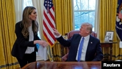 FILE - U.S. President Donald Trump confers with White House Communications Director Hope Hicks, at the White House in Washington, January 17, 2018.
