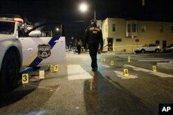 An investigator walks through the scene of a shooting, Jan. 8, 2016, in Philadelphia.