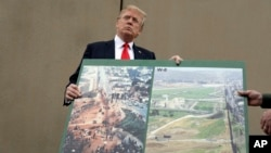 President Donald Trump holds an image of the border area as speaks during a tour as he reviews border wall prototypes, March 13, 2018, in San Diego, California. Trumps warns Mexico, April 3, 2018, that its free trade agreement would be jeopardized if it does not stop a caravan of Central American immigrants before it reaches the border with the U.S.