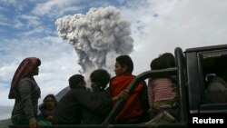 Warga desa duduk di truk saat melakukan evakuasi ke tempat aman, menyusul letusan Gunung Sinabung (24/11) di desa Aman Teran, kabupaten Karo, Sumatera Utara. (Reuters/YT Haryono)