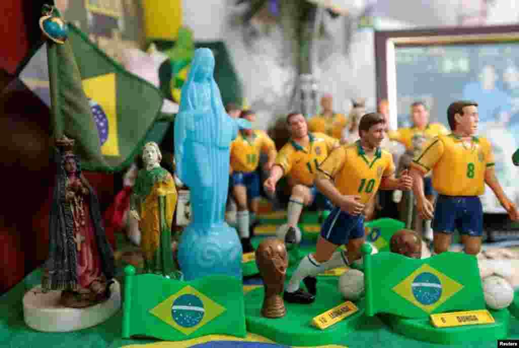 O ditado diz que Deus é brasileiro, Marilza juntou as suas figuras religiosas com os bonequinhos da equipa de futebol, em Brasília, Maio 27, 2014. REUTERS/Joedson Alves