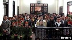Dalam foto yang diambil oleh Kantor Berita Vietnam ini, para tergugat berdiri di depan dermaga di sebuah pengadilan di provinsi Nghe An, sekitar 300 kilometer selatan Hanoi, 9 Januari 2013. (REUTERS/Nguyen Van Nhat/Vietnam News Agency). Vietnam kembali mengadili 22 aktivis demokrasi atas tuduhan subversi, Senin (27/1).
