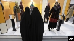 FILE - Head-to-toe veiled Iranian women look at mannequins in a women's dress show in Tehran, Iran, March 3, 2012.