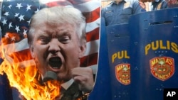 Protesters burn a portrait of U.S. President Donald Trump in front of riot police during a rally in front of the U.S. Embassy in Manila, Philippines, Feb. 4, 2017. The protesters were criticizing Trump's anti-immigration stance.