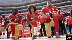 FILE - From left, San Francisco 49ers outside linebacker Eli Harold, quarterback Colin Kaepernick and safety Eric Reid kneel during the national anthem before an NFL football game against the Dallas Cowboys in Santa Clara, California, Oct. 2, 2016.