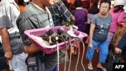 Seorang penjual menawarkan tikus panggang kepada para pembeli di sebuah pasar di Tomohon, Sulawesi Utara, 18 Februari 2017. (Foto: AFP)