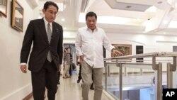 菲律宾总统府摄影部提供的照片显示,菲律宾总统杜特尔特(左)与来访的日本外相岸田文雄走在达沃市总统宾馆的行政厅内。(2016年8月11日)