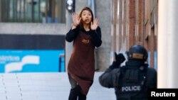 15일 호주 시드니의 한 카페에 감금되었던 인질 중 한 명이 탈출해 경찰쪽으로 달려오고 있다.
