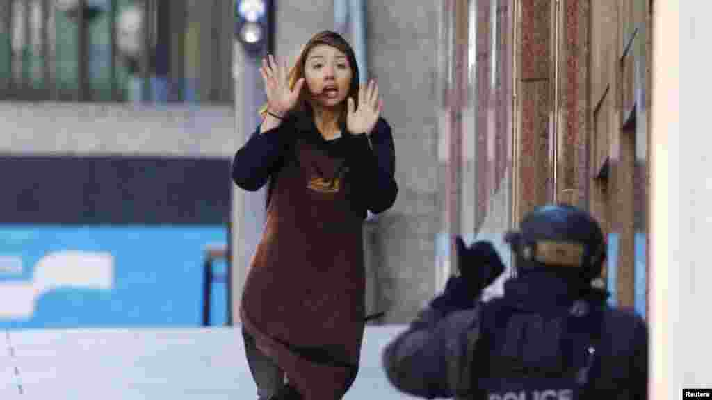 A hostage runs toward a police officer outside Lindt cafe, where other hostages are being held, in Martin Place in central Sydney, Australia, Dec. 15, 2014.