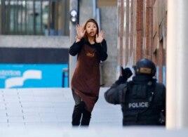 Một con tin chạy về phía cảnh sát đang bao vây bên ngoài quán café Lindt ở khu vực Martin Place, Sydney, Australia, 15/12/2014.
