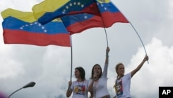 FILE - Patricia Ceballos, wife of jailed opposition leader Daniel Ceballos, left, opposition leader Maria Corina Machado, center, and Lilian Tintori, wife of jailed opposition leader Leopoldo Lopez lead a protest along a main road to demand a recall referendum against Venezuela's President Nicolas Maduro in Caracas, Venezuela, Oct. 22, 2016.