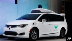 FILE - A Chrysler Pacifica hybrid outfitted with Waymo's suite of sensors and radar is displayed at the North American International Auto Show in Detroit. Google is partnering with AutoNation, the country's largest auto dealership chain, in its push to build a self-driving car. AutoNation said Thursday, Nov. 2, that its dealerships will provide maintenance and repairs for Waymo's self-driving fleet of Chrysler Pacifica vehicles.