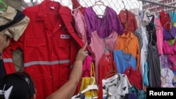 FILE -- A customer looks at PDVSA overalls for sale at a market in Maracaibo, Venezuela, Sept. 11, 2016.