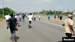 A screen grab shows people running during a protest in Abuja, Nigeria, Sept. 28, 2021.