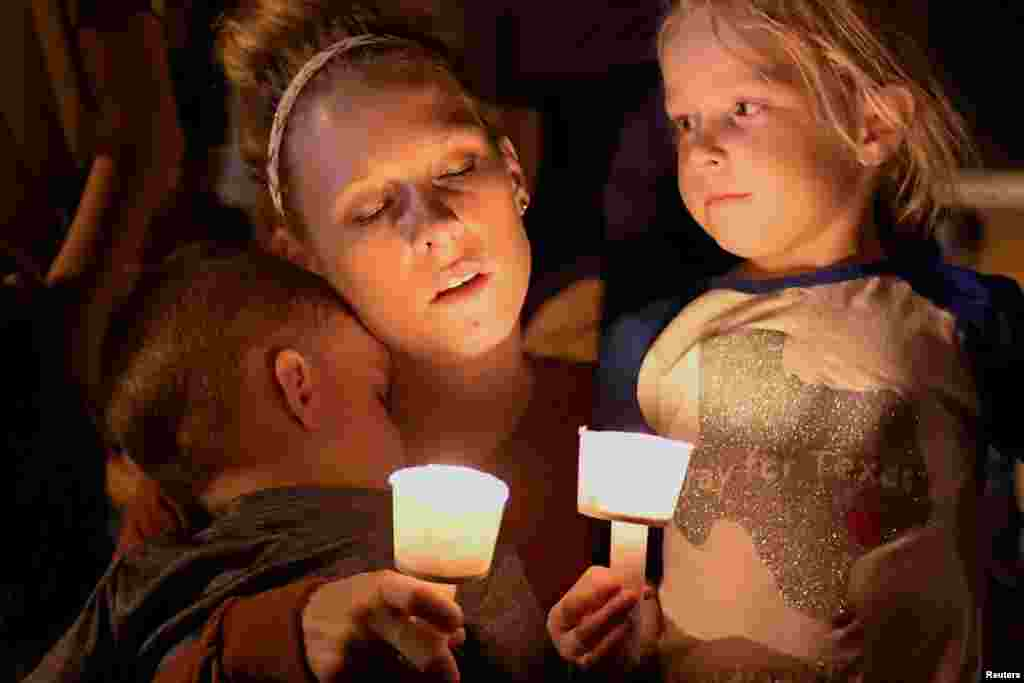 A woman and her children take part in a vigil for victims of a mass shooting in Sutherland Springs, Texas, Nov. 5, 2017.