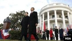 Prezidan ameriken an Barack Obama ak Prezidan Hu Jintao k ap mache nan lakou lamezon blanch aprè seremoni ki fèt pou resevwa prezidan chinwa a