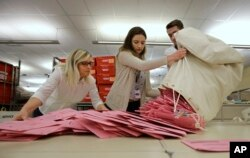 Election workers Heidi McGettigan, left, Margaret Wohlford, center, and David Jensen, unload a bag of ballots brought in a from a polling precinct to the Sacramento County Registrar of Voters office in Sacramento, Calif., June 5, 2018.