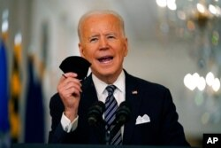 President Joe Biden holds up his face mask as he speaks about the COVID-19 pandemic during a prime-time address from the East Room of the White House, March 11, 2021.