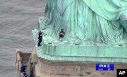 4일 미국 뉴욕시 '자유의 여신상' 위에 여성이 앉아있는 가운데 경찰이 사다리에 올라 타 여성을 설득하고 있다.