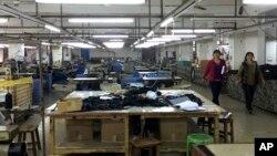 中國廣東省中山市南朗鎮翠亨制包廠工人罷工,幾名工人走過車間里處於停工狀態的工作台,2015年3月26日(資料圖片)
