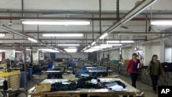 中国广东省中山市南朗镇翠亨制包厂工人罢工,几名工人走过车间里处于停工状态的工作台,2015年3月26日(资料图)