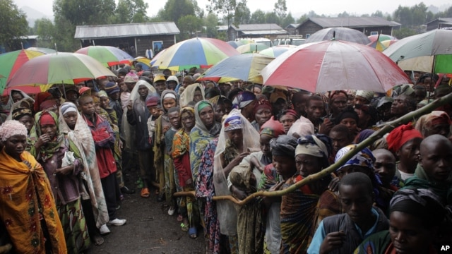 Internally displaced Congolese men and women wait for a World Food Program energy biscuits to be distributed in Kibati, north of Goma, eastern DRC, August 8, 2012.