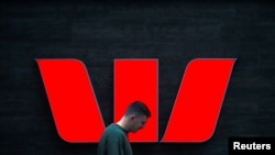 A pedestrian looks at his phone as he walks past a logo for Australia's Westpac Banking Corp located outside a branch in central Sydney, Australia, November 5, 2018. REUTERS/David Gray