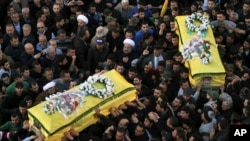Shi'ite militant group Hezbollah's fighters and supporters carry the coffins of a father and son, wrapped in a Hezbollah flag, during their funeral procession in the southern town of Ghaziyeh, Lebanon, Jan. 21, 2015.