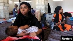 Una niña yemenita sostiene a un bebé en un refugio temporal en el puerto de Bosasso, Somalia.