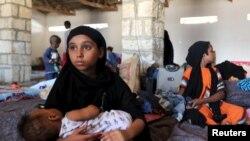 一名手抱女嬰的也門婦女逃避戰火,逃到位於索馬里的一個難民營。