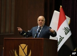 FILE - Iraq Prime Minister Haider al-Abadi gestures, during a press conference, in Baghdad, Iraq, Dec. 9, 2017.