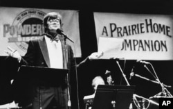 Radio host Garrison Keillor gestures to his audience during the first show in the newly remodeled World Theatre in St. Paul, Jan. 11, 1986. (AP/file)