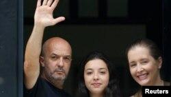 El excomisionado Iván Simonovis saluda desde un balcón de su casa en Caracas, junto a su hija Ivana y su esposa Bony Pertinez.