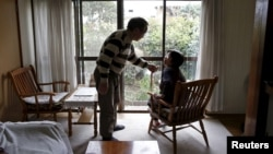 FILE - 72-year-old Kanemasa Ito and his 68-year-old wife Kimiko chat at their home in Kawasaki, south of Tokyo, Japan.