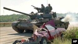 """Arhiva - Hrvatski tenk prolazi pored uništenog automobila srpskih civila, nakon akcije hrvatskih snaga """"Oluja"""", 10. avgusta 1995. (AP)"""