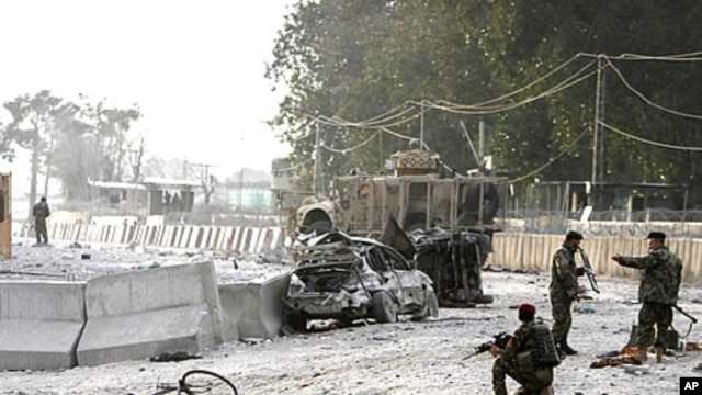 Afghan soldiers secure the scene of a suicide attack at the gate of an airport in Jalalabad, Nangarhar province east of Kabul, Afghanistan, February 27, 2012.