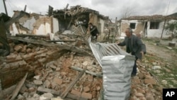 Villagers check damaged houses in Gerdec, Albania, March 17, 2008 after an explosion at a munitions depot. A U.S.-funded program assisted with cleanup.