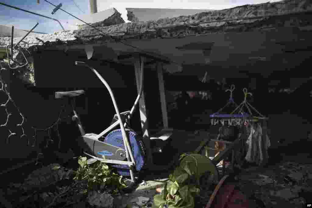 Una bicicleta estacionaria se observa donde el techo de una casa se derrumbó junto a la sala de juegos de una vivienda ubicada en el segundo piso, después de un terremoto en Guánica, Puerto Rico, el lunes 6 de enero de 2020.