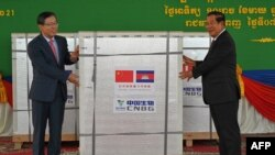 China's ambassador to Cambodia Wang Wentian (L) hands over a shipment of Sinopharm Covid-19 coronavirus vaccine to Cambodian Prime Minister Hun Sen (R) during a ceremony at Phnom Penh International Airport in Phnom Penh on February 7, 2021. (Photo by TANG CHHIN Sothy / AFP)