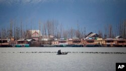 Kashmiri Muslims cross the Dal Lake on a small boat as migratory birds move on the water surface in Srinagar, India, Wednesday, Feb. 25, 2015.